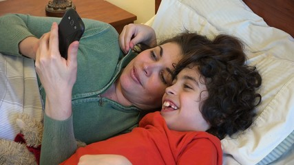 Single mother and son checking a smartphone in bed