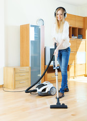 Woman in headphones with vacuum cleaner