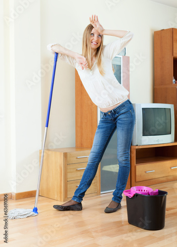 fatigue long-haired woman washing floor with mop