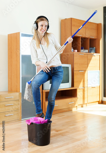 cheerful woman in headphones  with mop