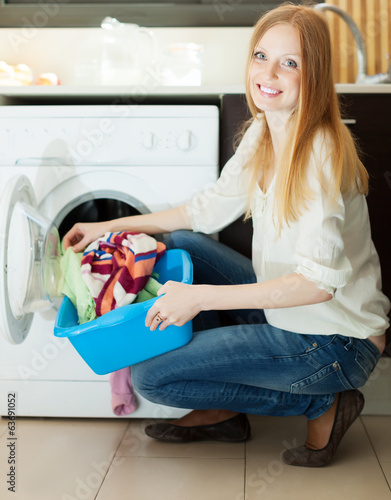 Long-haired blonde woman using washing machine