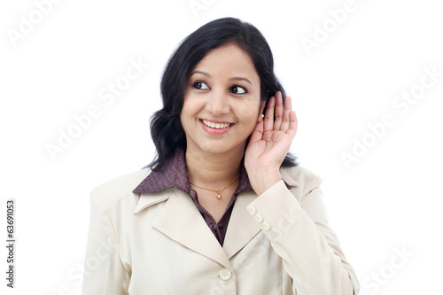 Young business woman listening against white