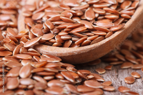 Flax seeds in a wooden spoon macro on a table. horizontal