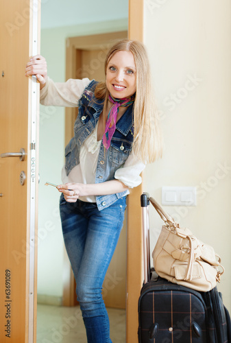 positive woman with luggage loocking door