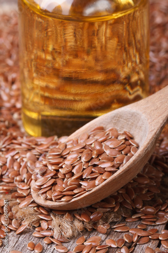 Flax seed in a wooden spoon and oil macro