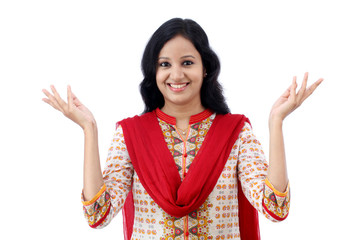 Happy young woman gesturing an open hand against white