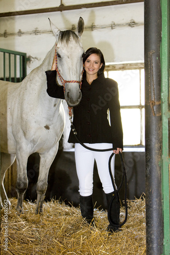 equestrian with horse in stable