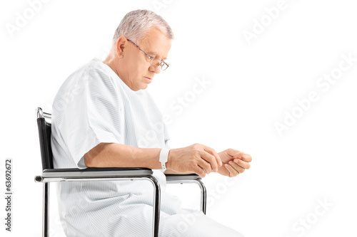 Sad mature man sitting in a wheelchair