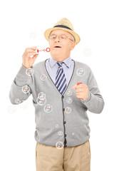 Senior gentleman blowing bubbles