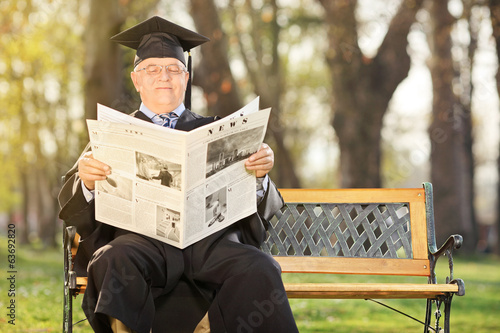 Mature college professor reading newspaper in park