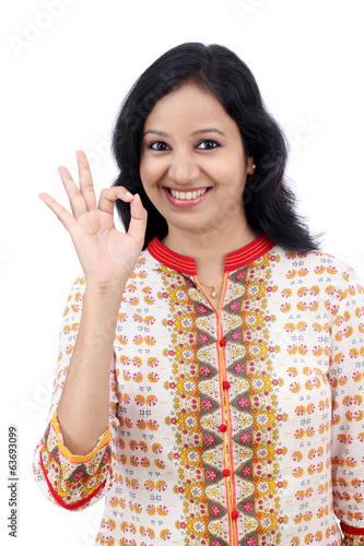 Happy young woman making Ok gesture
