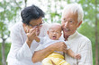 Asian crying baby comforted by grandparents at outdoor garden
