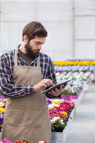 Male garden worker using tablet at greenhouse.
