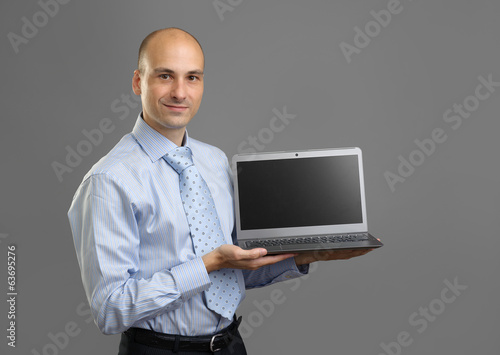 Sales man presenting laptop over gray background
