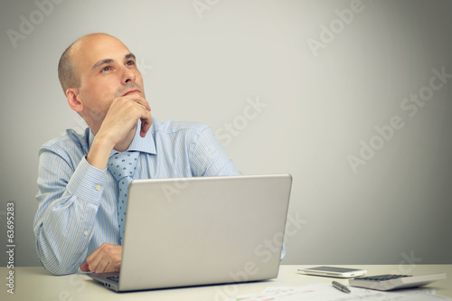 Thoughtful business man working on a laptop