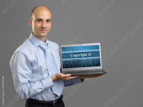 Businessman with laptop. Copyright concept
