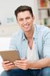 entspannter mann mit tablet-pc zu hause