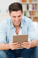 mann liest zuhause am tablet-pc