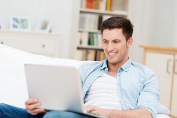 junger mann mit laptop auf dem sofa