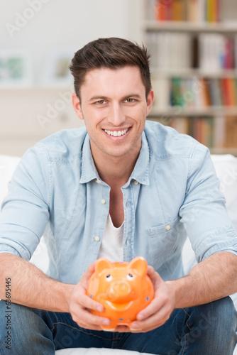 lächelnder mann hält sparschwein in händen