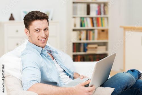 mann sitzt auf dem sofa mit seinem notebook