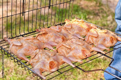 Raw marinated quail on the grill
