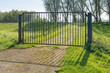 Closed iron gate in a rural landscape