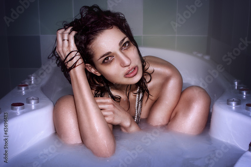 beautiful young woman in the bath with milk