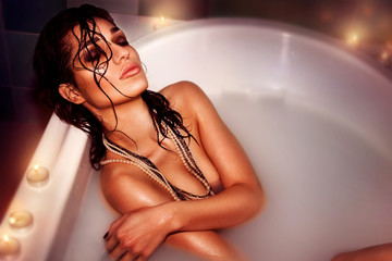 beautiful young woman in the bath with milk with candles