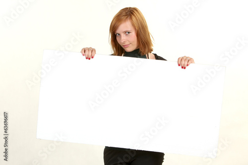 Young business woman holding empty white board for your sign.