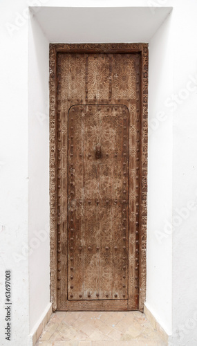 Ancient wooden door with Arabic carving relief pattern. Tangier,
