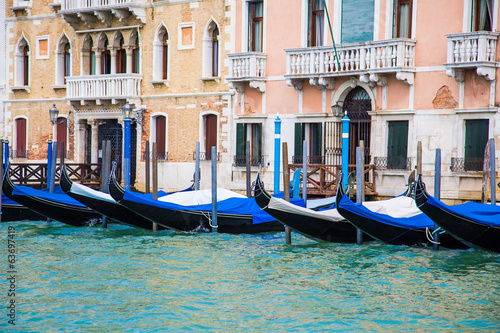 Black and Blue Gondolas Along Venice Canal