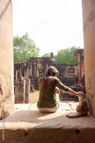 A woman is touching a cat at historical park