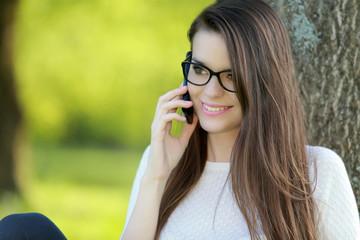 Jeune femme souriante téléphonant dans un jardin