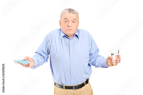 Confused senior man with pills and glass of water