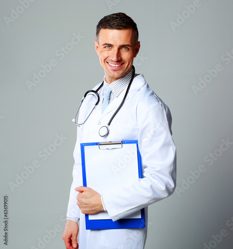 Happy male doctor holding empty clipboard on gray background