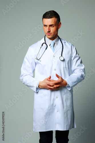 Portrait of a pensive male doctor on gray background