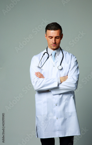 Male doctor standing with closed eyes on gray background