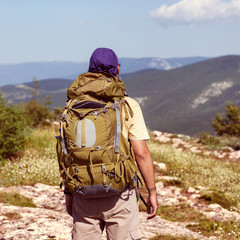 Hiker with backpack standing on top of a mountain