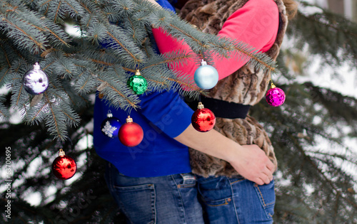 Young women and men stand near Christmas tree with snow.