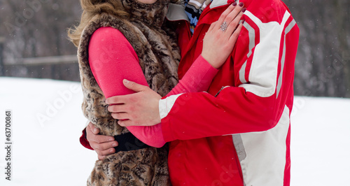 Young lovers woman and man in winter park