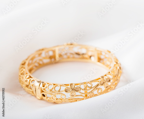 gold bracelet on white cloth