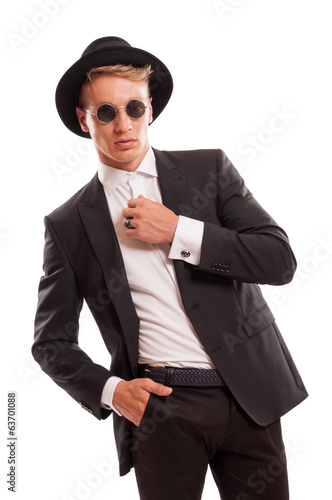 Elegant male model wearing a fancy hat and some round sun glasse