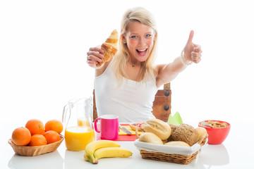 Frau beim Frühstück zeigt Daumen hoch