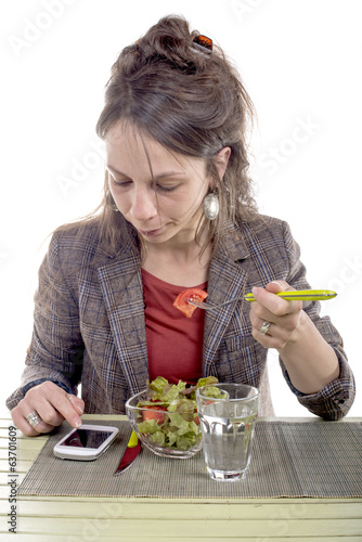 Portrait of a young business woman eating vegetable salad.