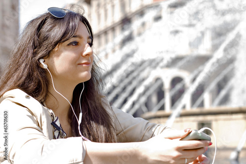 young girl with long black jair listening music through smart ph