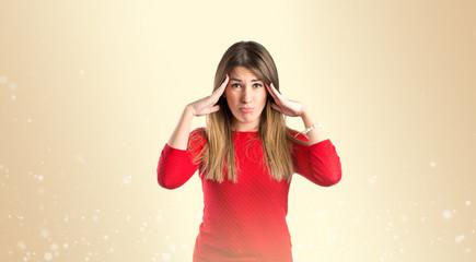 Cute girl with headache over isolated ocher background