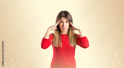 Cute girl with headache over isolated ocher background