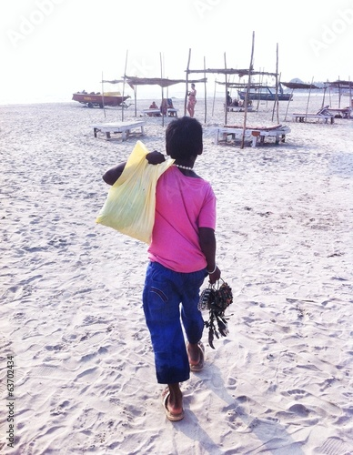 boy selling goods on the beach of Goa