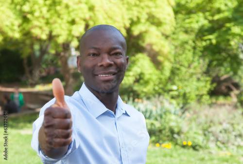 Sporty african man in a park showing thumb up